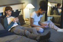Couple using mobile phones in bedroom at home — Stock Photo