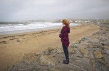 Femme rousse réfléchie debout dans la plage de sable . — Photo de stock