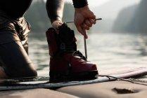 Partie médiane de l'homme réparant le wakeboard à la rivière — Photo de stock
