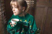 Femme regardant par la fenêtre tout en prenant un café à la maison — Photo de stock