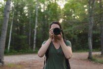 Женщина щелкает фотографии с камерой в лесу — стоковое фото