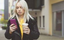 Bella donna che utilizza il telefono cellulare mentre prende il caffè — Foto stock