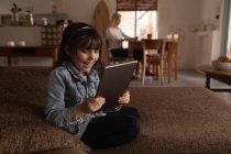 Ragazza che utilizza tablet digitale in soggiorno a casa — Foto stock