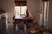 Thoughtful woman using laptop at home — Stock Photo