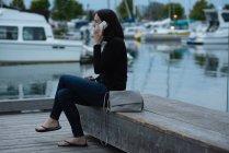 Vista lateral de la mujer hablando en el teléfono móvil cerca del puerto - foto de stock