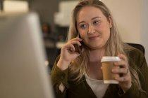 Exécutif parler téléphone mobile tout en buvant le café au bureau — Photo de stock