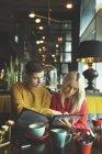 Couple discutant sur la carte de menu dans le café — Photo de stock