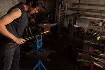 Atento metaleiro fêmea moldar ferradura na fábrica — Fotografia de Stock