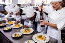 Group of chef garnishing food on plates — Stock Photo
