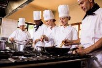 Groupe de préparer un repas dans la cuisine de chef — Photo de stock
