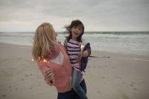 Felice madre e figlia che tengono scintille in spiaggia — Foto stock