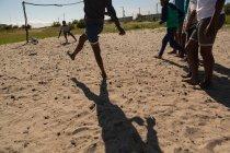 Crianças jogando futebol no chão em um dia ensolarado — Fotografia de Stock