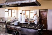 Группа шеф-поваров, работающих на кухне в ресторане — стоковое фото