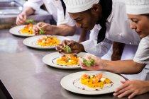 Gruppe von Koch Essen auf Tellern garnieren — Stockfoto