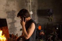 Joven hembra metalúrgica hablando por teléfono móvil mientras trabaja en fábrica - foto de stock