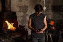 Joven hembra metalúrgica usando teléfono móvil en fábrica - foto de stock