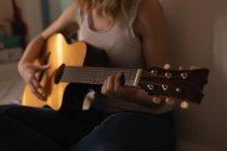 Mittelteil der Frau spielt zu Hause im Schlafzimmer Gitarre — Stockfoto