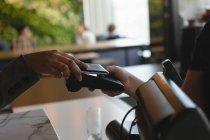 Крупный план женщины, платящей мобильным телефоном по технологии NFC у кассы — стоковое фото