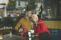 Giovane uomo baciare donna fronte in caffè — Foto stock