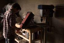 Женский кузнец с помощью точильного станка на заводе — стоковое фото