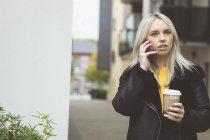 Linda mulher falando no telefone celular enquanto toma café — Fotografia de Stock