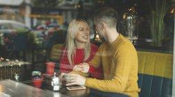 Glückliches Paar interagiert miteinander in Cafeteria — Stockfoto