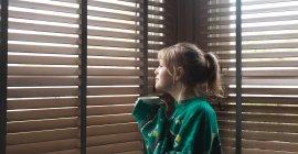 Vista lateral de la mujer mirando a través de la ventana mientras toma café en casa - foto de stock