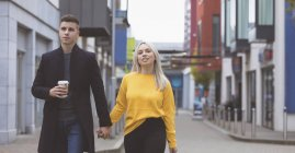 Young couple holding hand and walking on street — Stock Photo