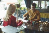 Joven pareja tener café en la cafetería - foto de stock