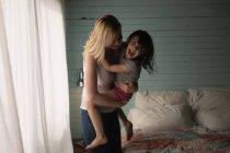 Madre e hija abrazando unos a otros en el dormitorio en casa - foto de stock
