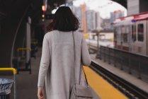 Vista posteriore della donna che cammina sulla piattaforma alla stazione ferroviaria — Foto stock