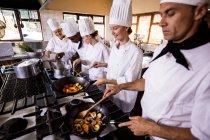 Grupo del cocinero preparando la comida en la cocina - foto de stock