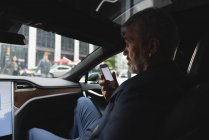 Side view of businessman talking on mobile phone in car — Stock Photo