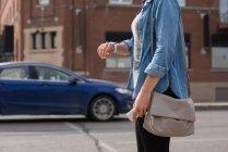 Sección media de la mujer comprobando el tiempo en smartwatch en la calle de la ciudad - foto de stock