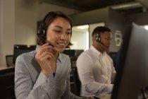 Dirigenti del servizio clienti che parlano in cuffia alla scrivania in ufficio — Foto stock