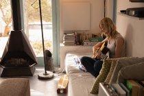 Красивая женщина играет на гитаре в спальне дома — стоковое фото