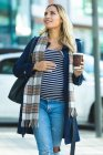 Beautiful pregnant woman walking on footpath with takeaway coffee in the city — Stock Photo