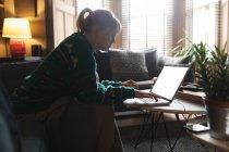 Donna che utilizza il computer portatile in soggiorno a casa — Foto stock