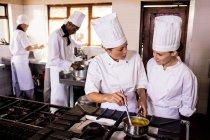 Chef mujer hablando mientras se prepara la comida en cocina de restaurante - foto de stock