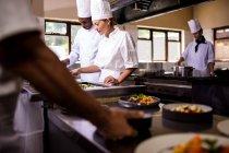 Chefs working in kitchen at restaurant — Stock Photo