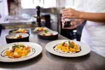 Metà di sezione di chef utilizza macinapepe in cucina al ristorante — Foto stock