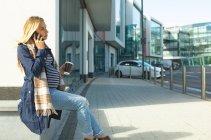 Mulher grávida falando no telefone celular na cidade em um dia ensolarado — Fotografia de Stock