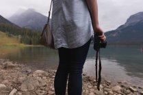 Metà sezione di donna stranding con fotocamera vicino al lago — Foto stock