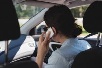 Вид сзади женщины, разговаривающей по мобильному телефону, сидящей в машине — стоковое фото