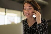 Souriant talking exécutif sur téléphone portable au bureau — Photo de stock