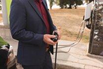 Sezione centrale dell'uomo d'affari che tiene la spina del caricabatterie alla stazione di ricarica — Foto stock