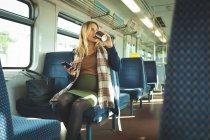 Беременная женщина пьет кофе во время использования мобильного телефона в поезде — стоковое фото
