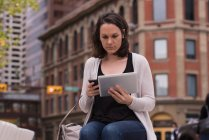 Mujer usando teléfono móvil y tableta digital en la ciudad - foto de stock