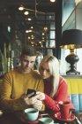Couple discutant sur téléphone portable dans le café — Photo de stock