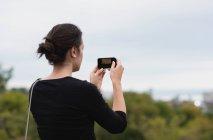 Задній вид жінка, натиснувши фотографій за допомогою мобільного телефону — стокове фото